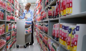 Woman filing medical records in a storage facility